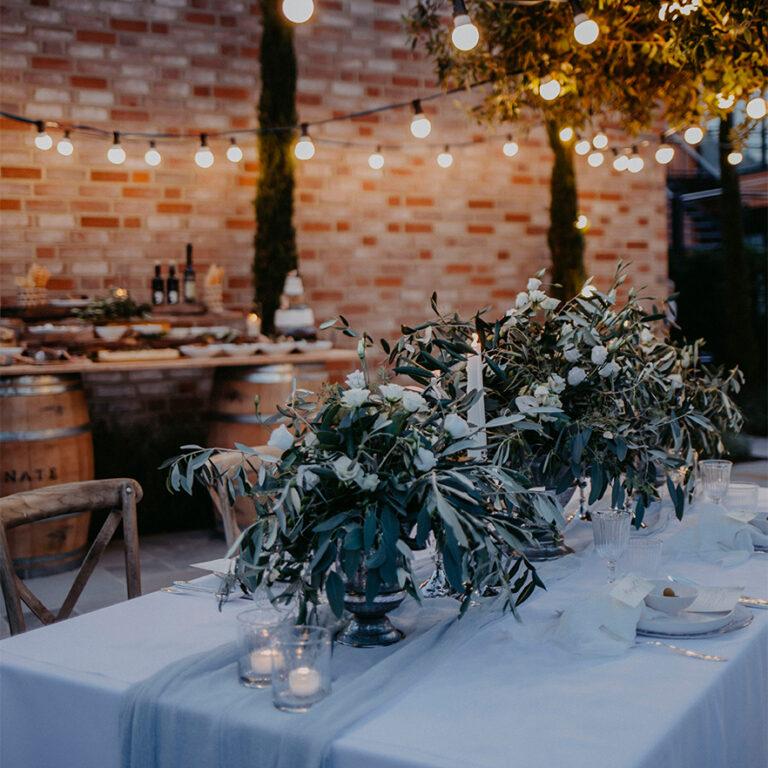 dekorierter Tisch mit vielen Blumen und LIchterketten