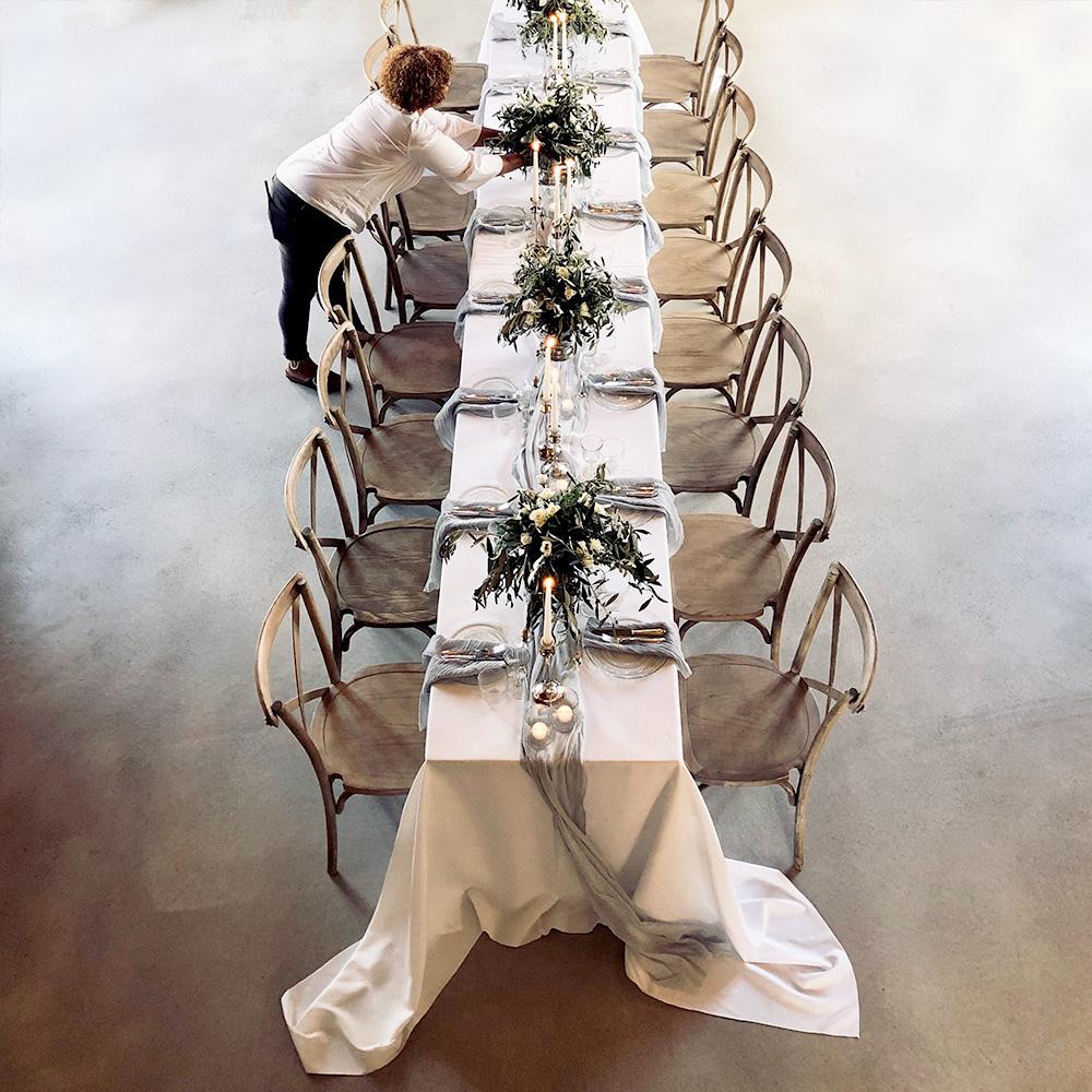 Frau Lehmann dekoriert eine lange Tafel mit Kerzen und Blumengestecken