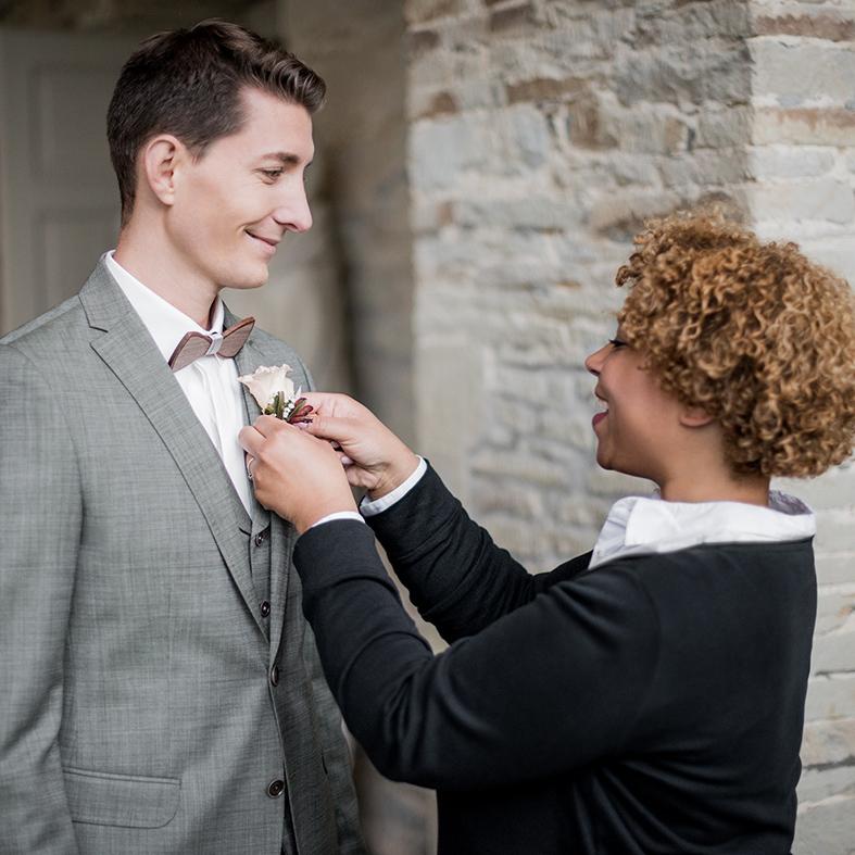 Frau Lehmann steckt einem Bräutigam ein Anstecksträußchen an