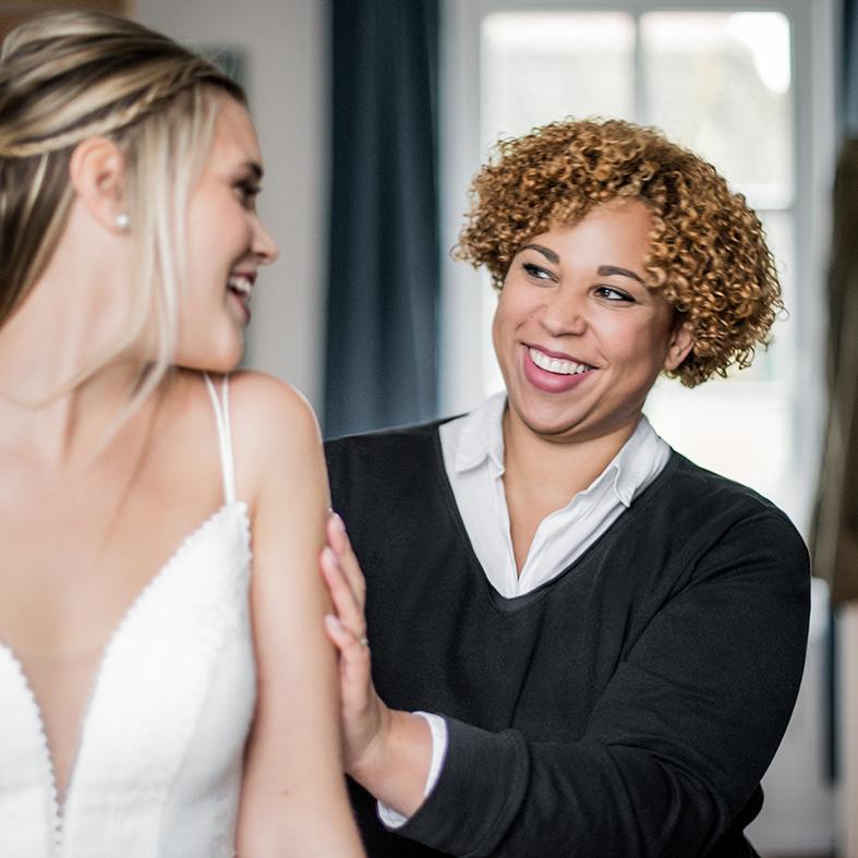 Frau Lehmann steht hinter einer Braut und sie lachen sich an