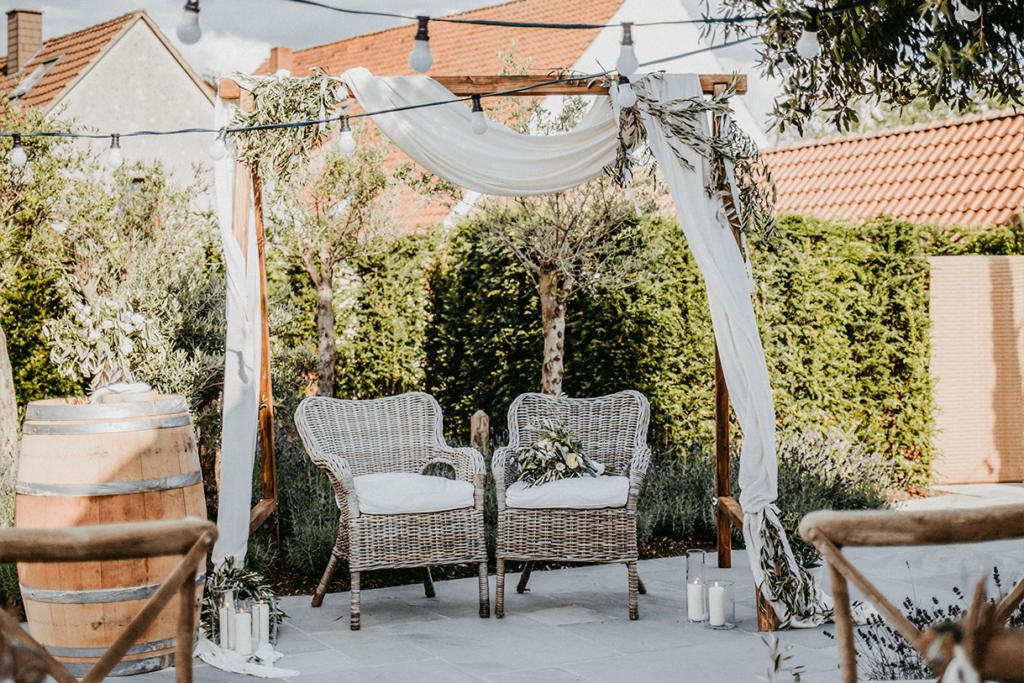 dekorierter Traubogen mit Korbstühlen für Brautpaar