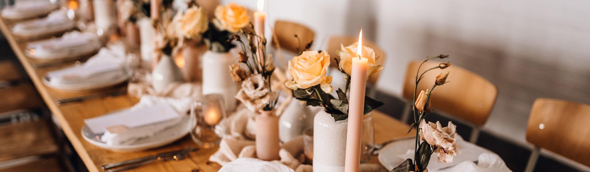 pfirsichfarben gedeckter Tisch mit Rosen und Kerzen