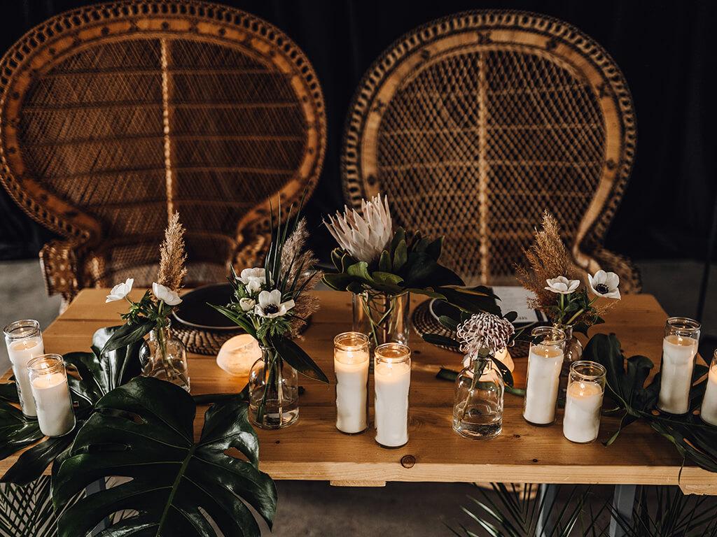 dekorierter Tisch mit Kerzen und Pfauenthrönen